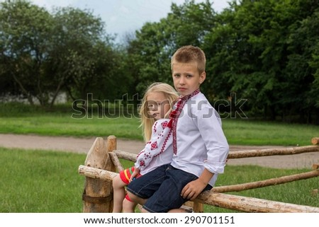 Children in ukrainian traditional clothes on the hedge in village