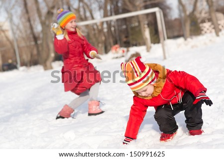 Children in Winter Park playing snowballs, actively spending time outdoors - stock photo