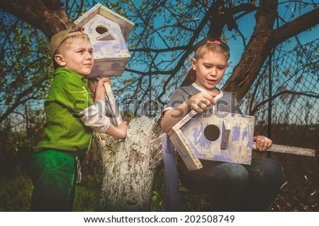 Children installing a self-made Bird House. - stock photo