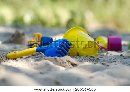 Children is plastic toys on the sand beach - stock photo
