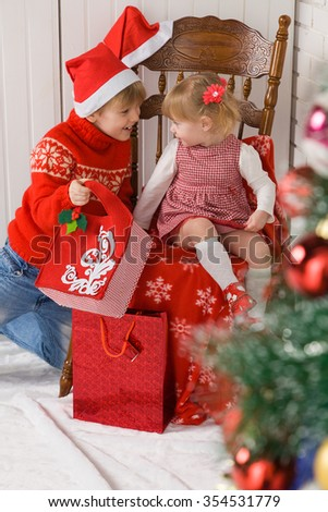 Children is sitting near a Christmas tree. They are opening their gifts with interest
