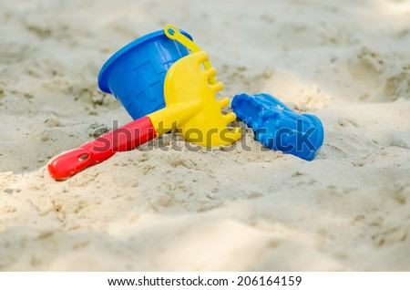 Children is toys on sand in the sandbox - stock photo