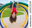 children kid girl upside down on a park playground ring game - stock photo