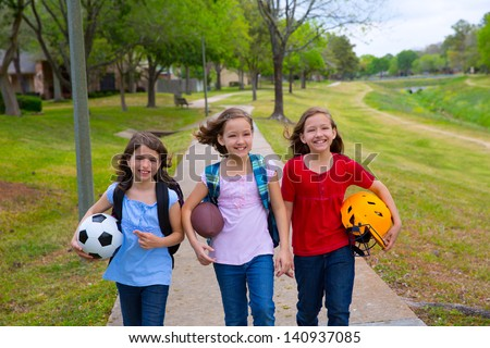 Children kid girls walking to school with sport balls folders and backpacks in outdoor park - stock photo