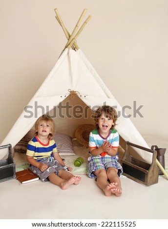 Children, kids playing at home indoors in a teepee tent - stock photo