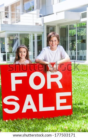 children kids standing outside their new house smiling, sister and brother hold for sale sign