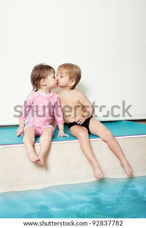 children kissing in the pool - stock photo
