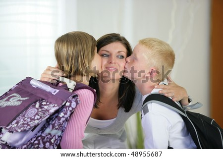 Children kissing their mother goodbye - stock photo