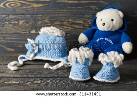 Children knitted garments for the boy. Hat and booties - stock photo
