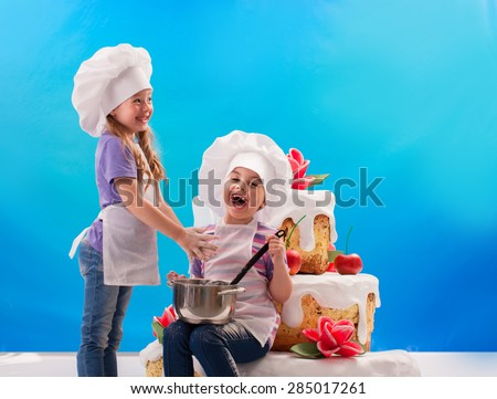 Children laugh, stirring cream on a background of a huge cake - stock photo