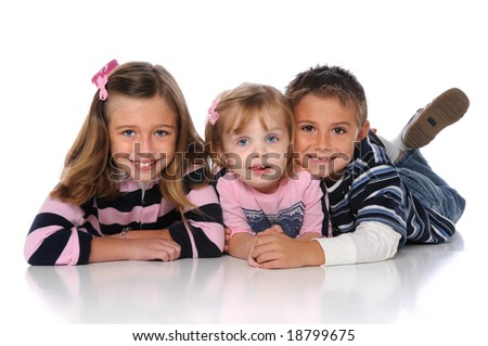 Children laying on the floor smiling over a white background