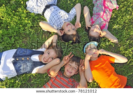 children laying together on ground - stock photo