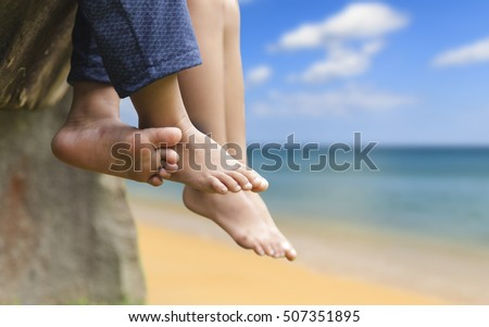 Children legs barefoot, Kids sitting dangling their feet at sea in summer concept for family, friends