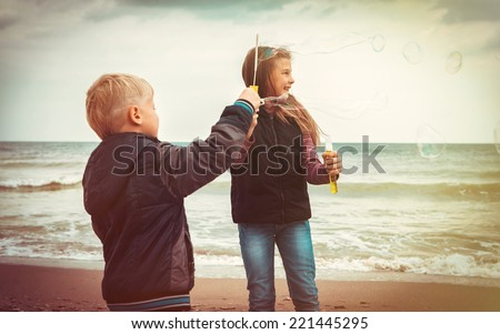 children let the bubbles on the sea shore - stock photo