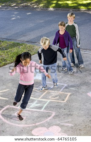 Children lined up on driveway, playing hopscotch.  Ages 7 to 9. - stock photo