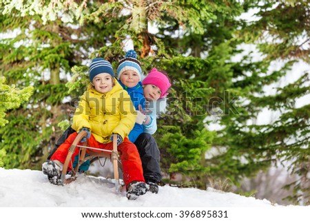 Children little boys and girl slide on sledge  - stock photo