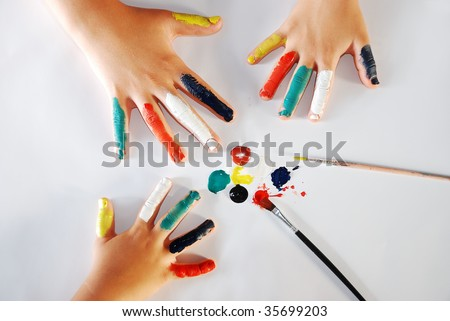 Children little hands playing with colors on white background - stock photo