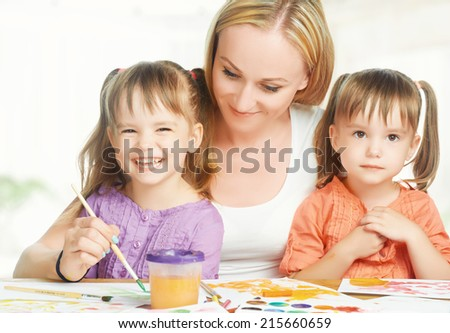 children little twin sisters draw paints with mother in kindergarten on a white background - stock photo