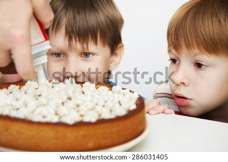 Children look at the cake, topped with whipped cream. - stock photo