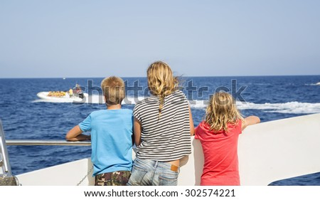Children look at the sea from the deck of a boat - stock photo