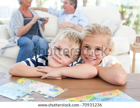 Children looking at the camera in the living room - stock photo