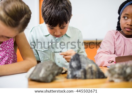 Children looking fossils with a magnifying glass at school
