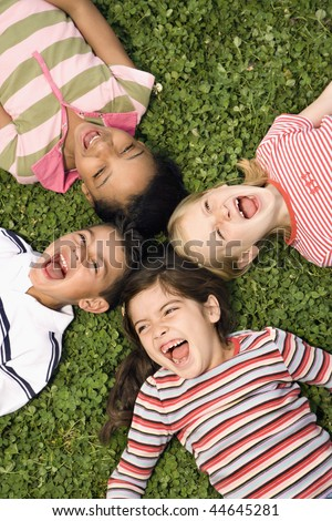 Children lying in clover screaming and laughing with heads together. Vertically framed shot. - stock photo