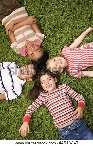 Children lying in clover with heads together. Vertically framed shot. - stock photo