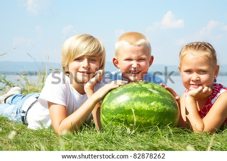 Children lying in grass with  red watermelon - stock photo