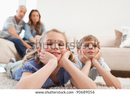 Children lying on a carpet while their parents are sitting on a sofa - stock photo