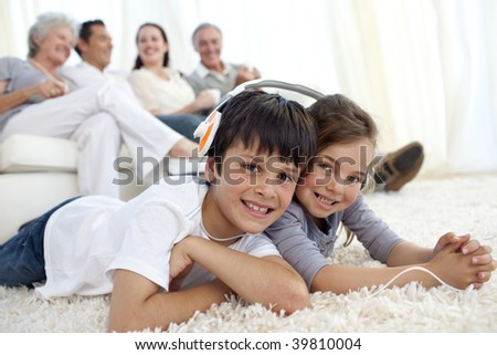 Children lying on carpet with their parents and grandparents in sofa at home - stock photo