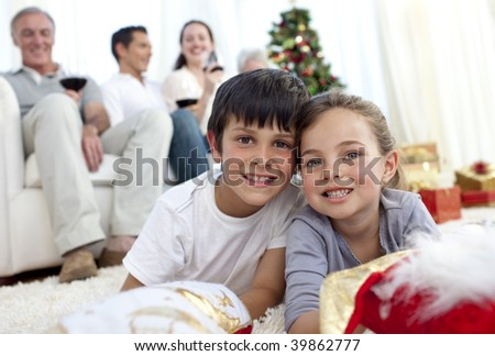 Children lying on floor at home with their family in Christmas