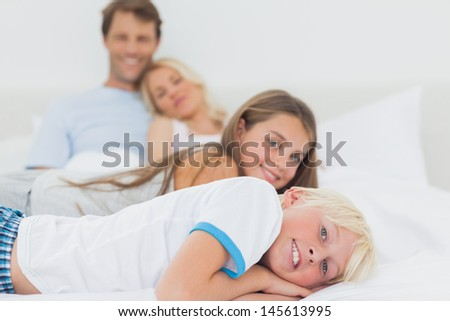 Children lying on the bed with their parents behind them - stock photo