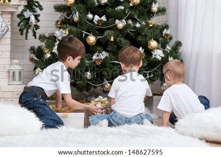 Children make out gifts at Christmas tree - stock photo