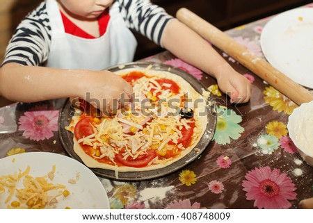 Children make pizza. Master class for children on cooking Italian pizza. Young children learn to cook a pizza. Kids preparing homemade pizza. Little cook. - stock photo