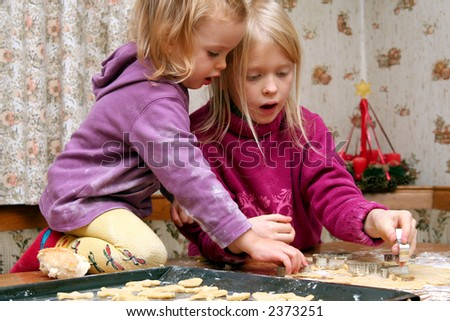 Children making christmas cookies in the kitchen - stock photo