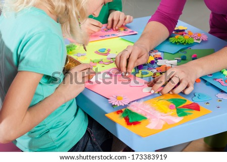 Children making decorations on colorful paper with art teacher - stock photo