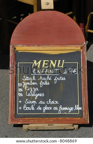 Children menu board in front of an restaurant in France - stock photo