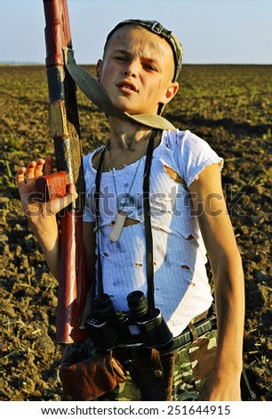 Children of war. The little boy weapon on the battlefield. - stock photo