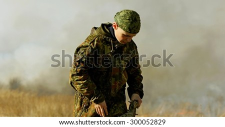Children of war. The little boy weapon on the battlefield. - stock photo