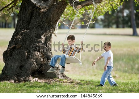 Children on a swing on a nature - stock photo