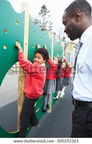 Children On Climbing Wall In School Playground At Breaktime - stock photo
