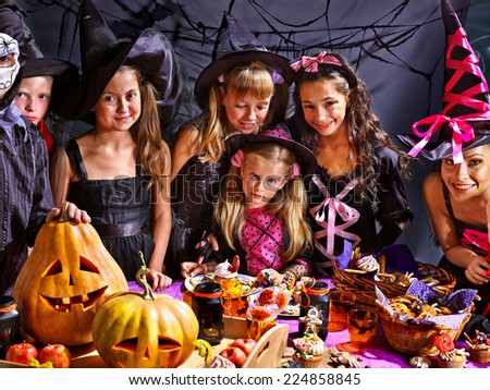 Children on Halloween party  sitting at trick or treat table. - stock photo