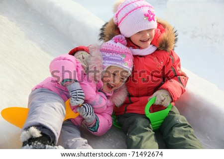 children on ice hill at winter - stock photo