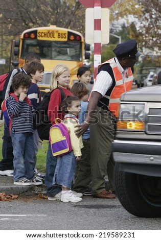 Children on street with crossing guard - stock photo