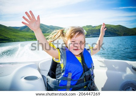children on the boat on the river in a sunny day. - stock photo