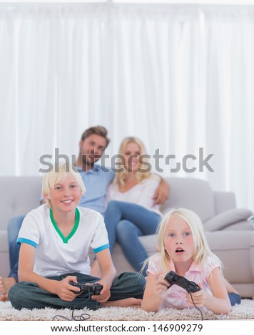 Children on the carpet playing video games in the living room while their parents are watching them - stock photo