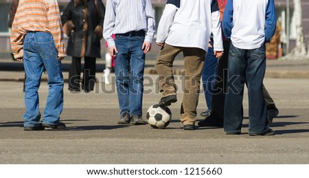 Children on the city area play football. - stock photo