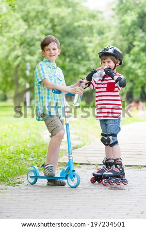 children on the rollers and the scooters drink bottled water - stock photo