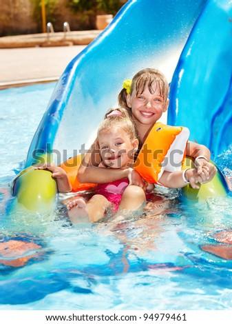 Children on water slide at aquapark. Summer holiday. - stock photo